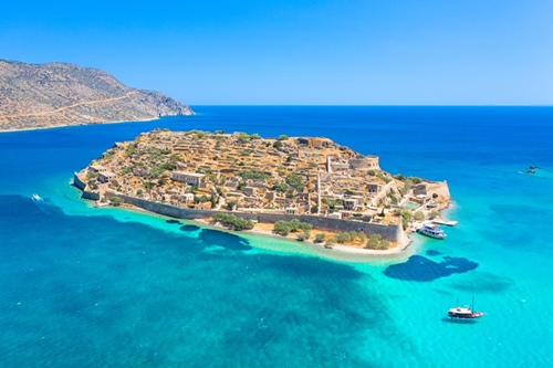 View of the island of Spinalonga with calm sea. Here were isolated lepers, humans with the Hansen's desease, gulf of Elounda, Crete, Greece.